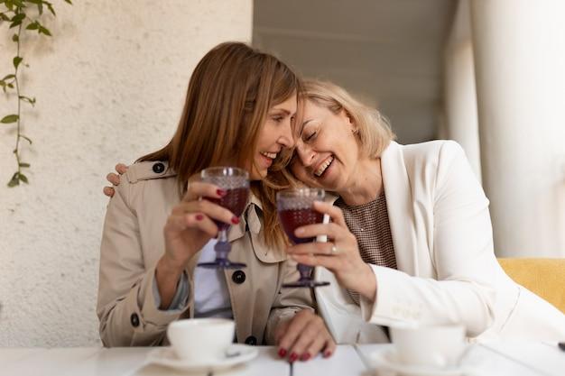Mujeres de tiro medio con bebidas Foto gratis