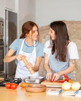 Mujeres de tiro medio en la cocina