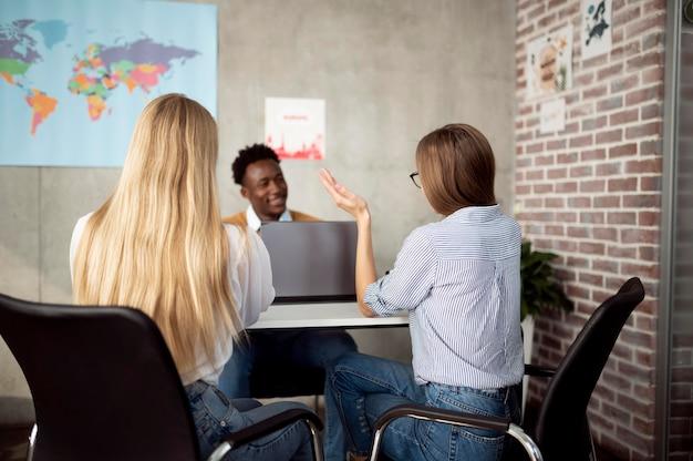 Mujeres de tiro medio discutiendo con el agente de viajes