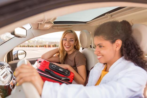 Mujeres de tiro medio con equipaje en coche