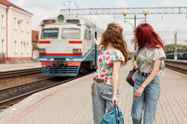 Mujeres de tiro medio en la estación de tren
