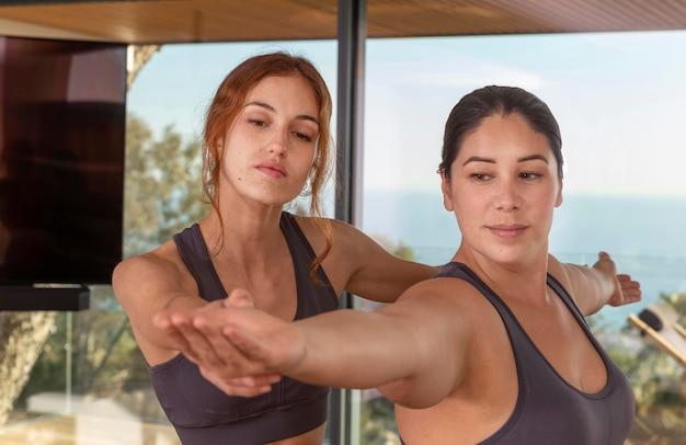 Mujeres de tiro medio haciendo yoga juntos
