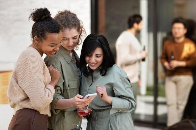 Mujeres de tiro medio mirando el teléfono