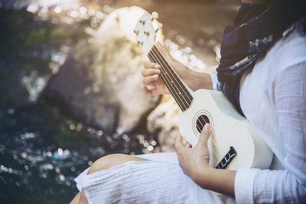 Las mujeres tocan el ukelele nuevo a la cascada.