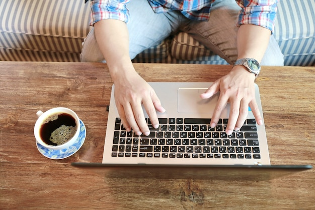 Mujeres tocando la pantalla y el hombre escribiendo portátil en la mesa de madera