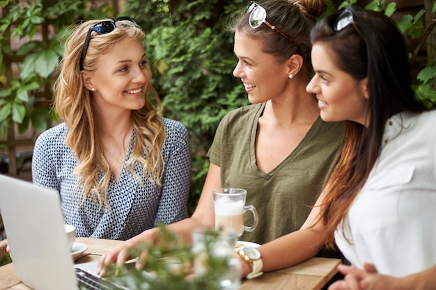 Mujeres tomando un café con amigos y usando una computadora portátil