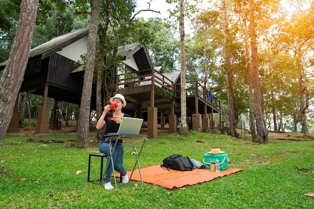 Mujeres tomando café en la mañana y trabajando en la computadora portátil en vacaciones