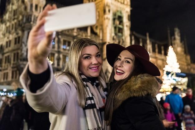 Mujeres tomando un selfie en el mercado de navidad en munich