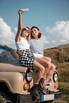 Mujeres tomando selfie mientras viaja en coche