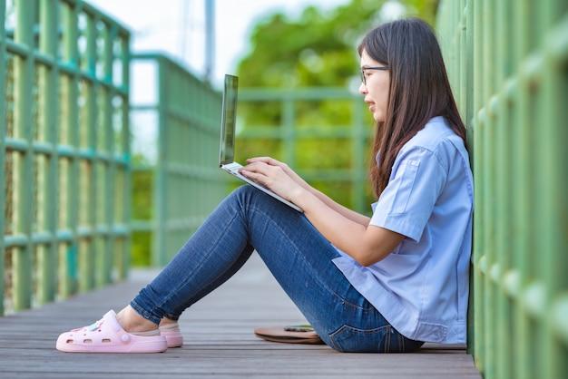 Mujeres trabajadoras asiáticas en un parque público que usan un teléfono inteligente y una computadora portátil estilo de vida moderno