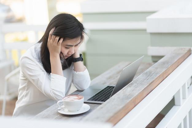 Mujeres trabajadoras pensando y trabajando con una computadora portátil en el café