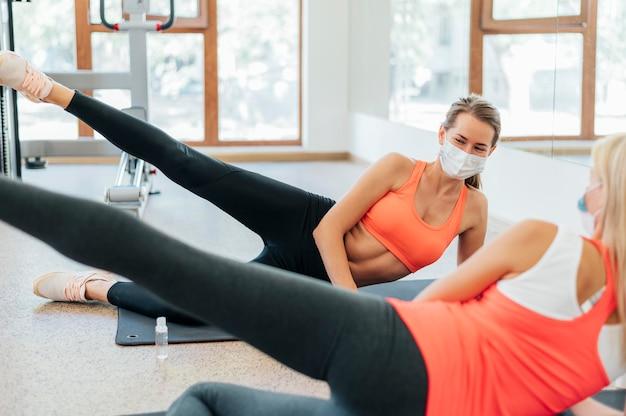 Mujeres trabajando en el gimnasio con máscara médica juntos