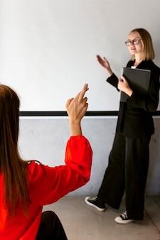 Mujeres en el trabajo usando lenguaje de señas