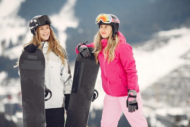 Mujeres en traje de snowboard. deportistas en una montaña con una tabla de snowboard en las manos en el horizonte. concepto de deportes