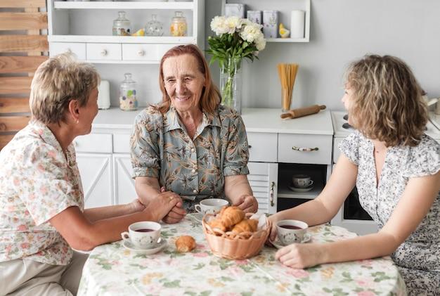 Mujeres de tres generaciones hablando algo durante el receso.