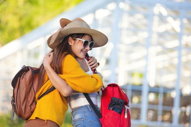 Mujeres turistas caminar sosteniendo los brazos