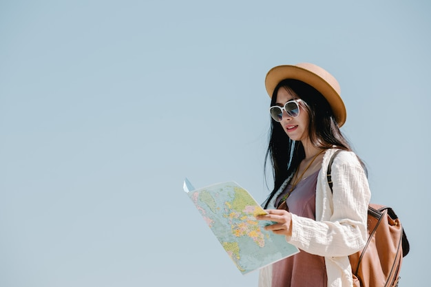 Mujeres turistas en mano tienen un feliz mapa de viaje.