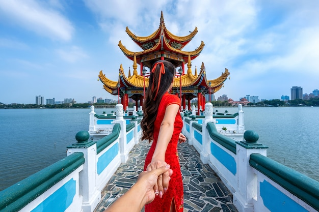Mujeres turistas que toman de la mano del hombre y lo llevan a las famosas atracciones turísticas de kaohsiung en taiwán.