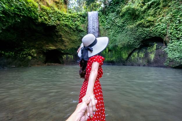 Las mujeres turistas sosteniendo la mano del hombre y lo llevan a la cascada tibumana en bali, indonesia
