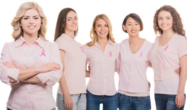 Mujeres unidas con cinta rosa de concientización sobre el cáncer de mama.
