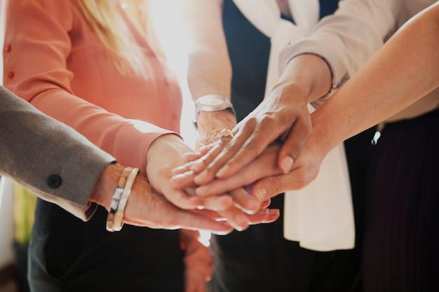 Mujeres uniendo sus manos en el medio