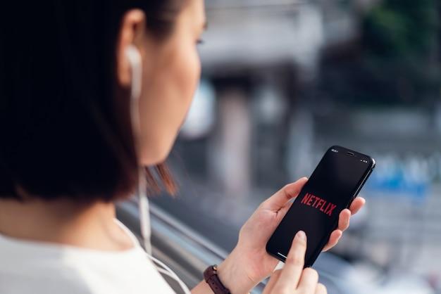 Las mujeres usan la aplicación netflix en la pantalla del teléfono inteligente.