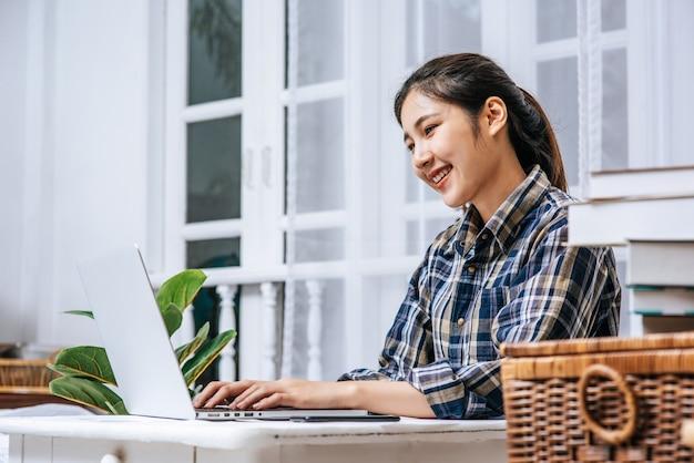 Las mujeres usan las computadoras portátiles en la oficina con placer.