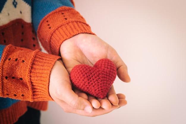Las mujeres usan la mano de la camisa tejida que sostiene el corazón rojo.
