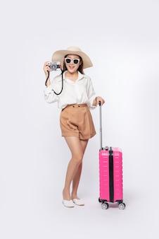 Las mujeres usan sombreros, anteojos, equipaje y llevan cámaras en el camino a viajar.