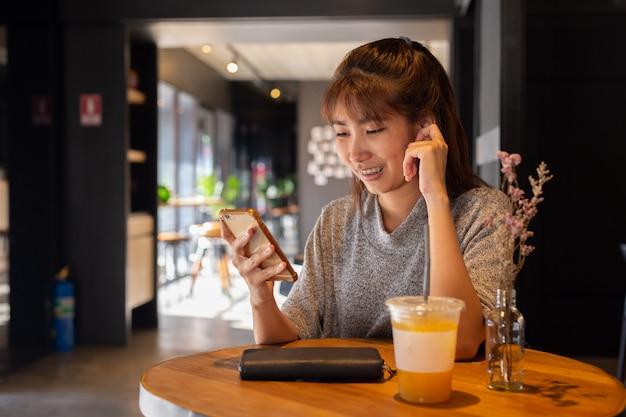 Las mujeres usan el teléfono inteligente en la cafetería