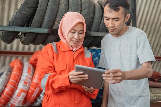 Mujeres con velo vistiendo uniformes wearpack mostrando tabletas digitales a consumidores en talleres