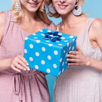 Mujeres vestidas elegantes que sostienen un regalo