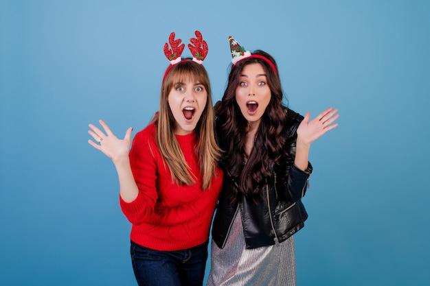 Mujeres vestidas con ropa de invierno y divertidos aros de navidad aislados sobre azul