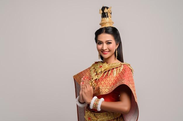 Mujeres vestidas con ropa tailandesa que rinden respeto, símbolo sawasdee
