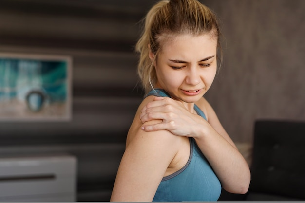 Mujeres vestidas con trajes deportivos que sienten dolor en el hombro después de hacer ejercicio en casa. el peligro de la autoformación