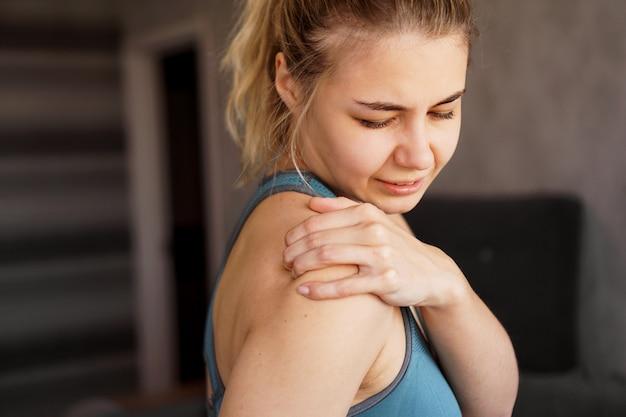 Mujeres vestidas con trajes deportivos sintiendo dolor en el hombro después del ejercicio en casa