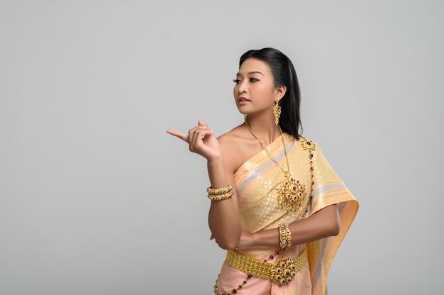 Mujeres vestidas con trajes tailandeses que son simbólicos, señalando con el dedo