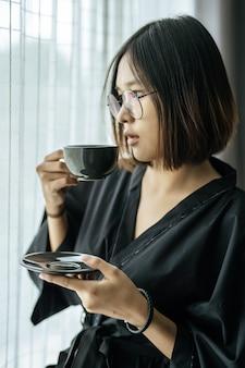 Mujeres vestidas con túnicas negras, entregando café en el dormitorio.