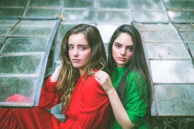 Mujeres con vestidos verdes y rojos mirando a la cámara
