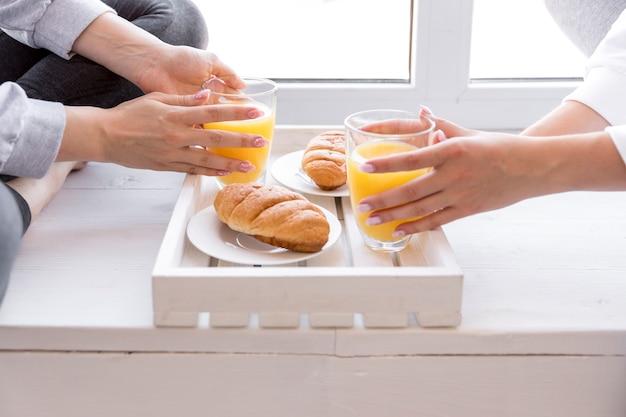 Mujeres de vista cercana que tienen jugo de naranja