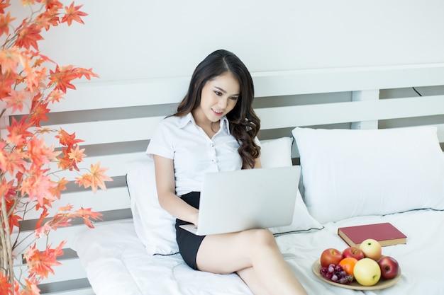 Las mujeres visten uniformes de estudiantes viendo una película desde una computadora portátil.