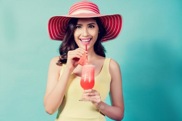 Las mujeres visten vestidos. ella estaba bebiendo batidos de sandía en el verano ella se siente refrescada.