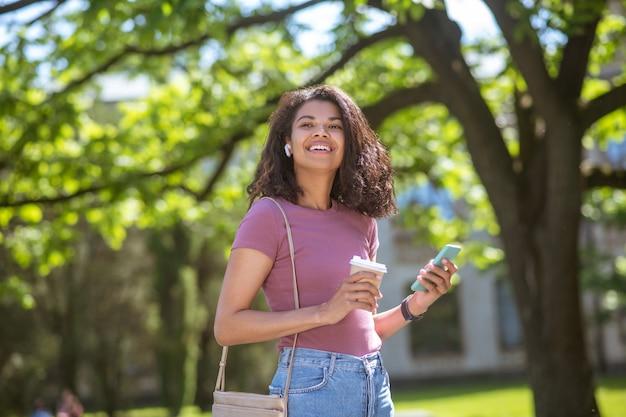 Mulata sonriente con una taza de café en las manos en el parque