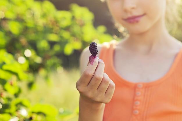 Mulberrie berrie maduro en mano de niña