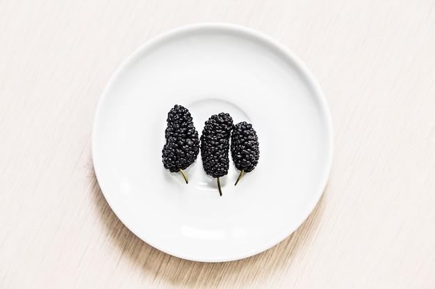 Mulberrie negra en un plato blanco