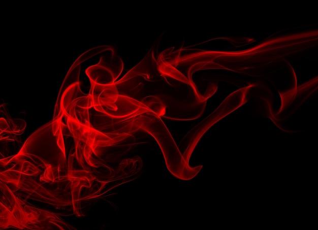 Mullidas bocanadas de humo rojo y niebla sobre fondo negro, diseño de fuego