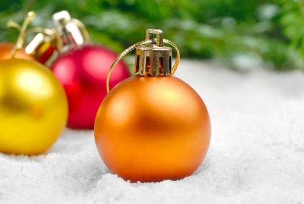 Multi color bolas de navidad en la nieve bajo pino
