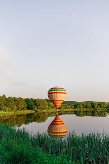 Multi color globo aerostático volando sobre el lago cerca del agua. vuelos en globo en la naturaleza.