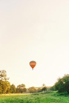 Multi color globo aerostático volando sobre el valle en el cielo al amanecer. viajes y deporte.