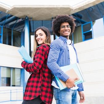 Multi étnica masculina y femenina de pie espalda con espalda frente a campus universitario